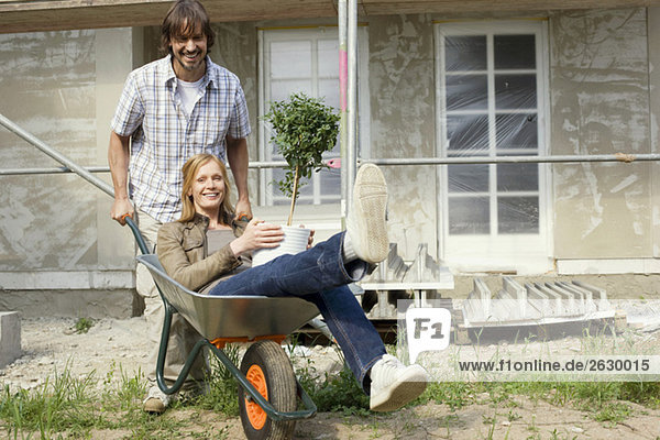 Young couple at construction site  man pushing woman in wheelbarrow