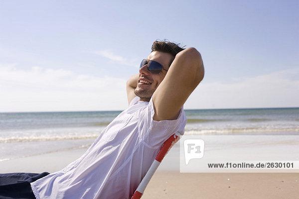 Deutschland  Ostsee  Junger Mann am Strand  lächelnd  Portrait