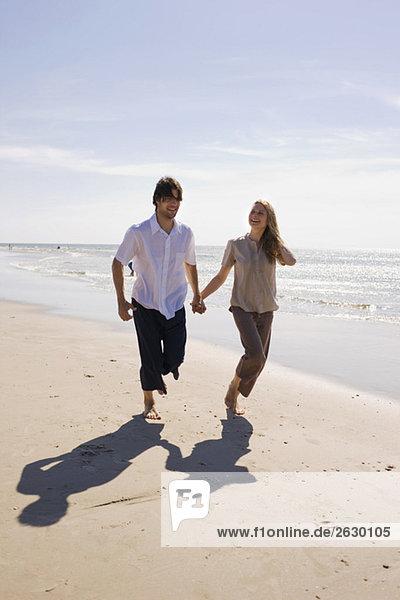 Deutschland  Ostsee  Junges Paar am Strand entlang  Händchen haltend