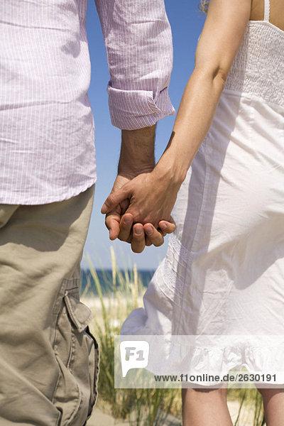 Deutschland  Ostsee  Paar hält Händchen  Rückansicht