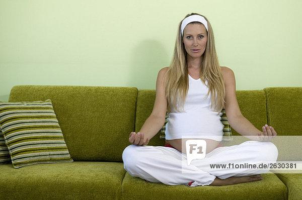 Schwangere Frau sitzt auf dem Sofa und übt Yoga. Schwangere Frau sitzt auf dem Sofa und übt Yoga.