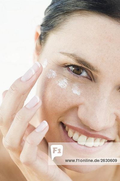 woman creaming face on beach