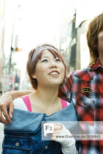 Young woman standing with boyfriend's arm around her shoulder  looking up  smiling  cropped view