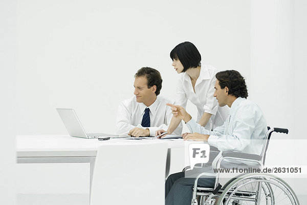 Profis  die zusammen auf den Laptop schauen  ein Mann im Rollstuhl sitzend