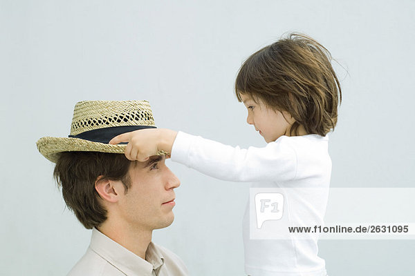 Kleiner Junge setzt Strohhut auf den Kopf seines Vaters  Seitenansicht