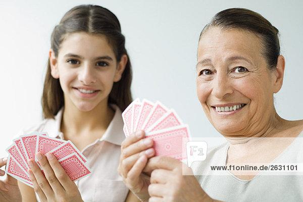 Großmutter und Enkelin spielen Karten und lächeln in die Kamera.