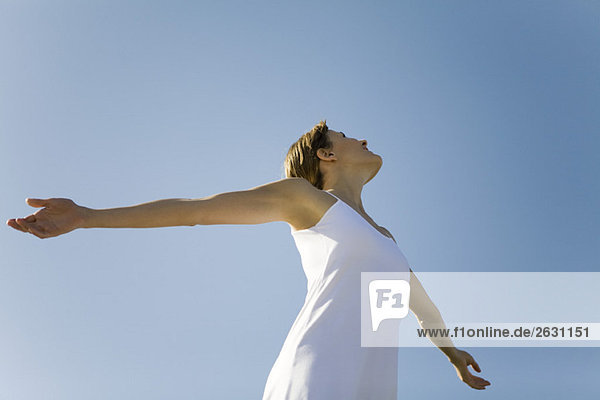 Woman with outstretched arms  looking up  low angle view