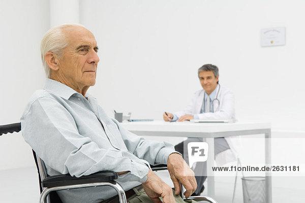 Senior-Patient im Rollstuhl  Arzt am Schreibtisch im Hintergrund