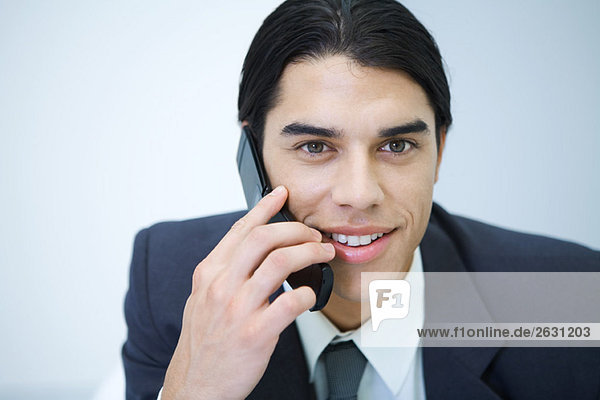 Young professional man holding cell phone  smiling  portrait