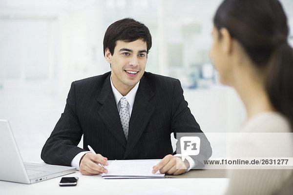 Geschäftsmann am Schreibtisch sitzend  mit Frau redend und lächelnd