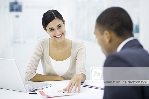Professional woman sitting with client at desk  discussing brochure