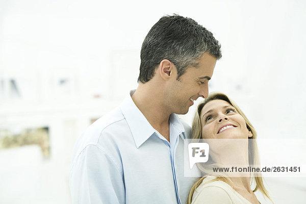Paar lächelt sich an  Frau lehnt sich an den Mann