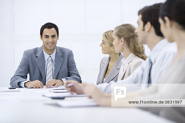Geschäftsmann sitzend mit Kollegen am Konferenztisch  lächelnd vor der Kamera