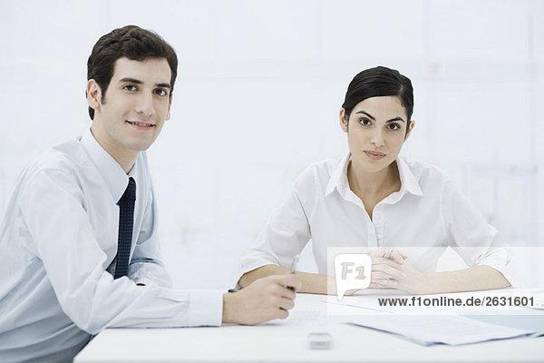 Profis sitzend mit Dokumenten  lächelnd vor der Kamera