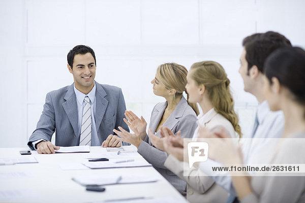 Geschäftsmann an der Spitze des Tisches  lächelnd  Kollegen klatschend