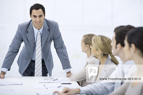 Geschäftsmann lehnt sich über den Tisch und spricht Kollegen an  lächelt in die Kamera