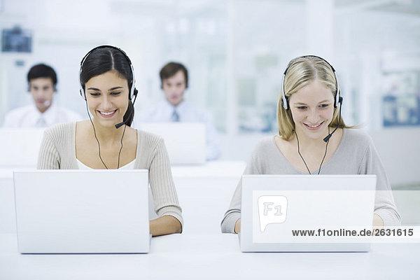 Telemarketer  die im Call Center arbeiten  lächelnd