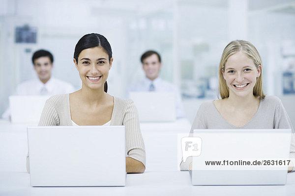 Professionelle Frauen  die Laptops benutzen  lächeln in die Kamera  Kollegen im Hintergrund