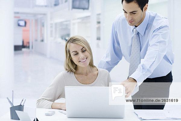 Profis  die zusammen auf den Laptop schauen  Mann  der über die Schulter der Frau schaut.