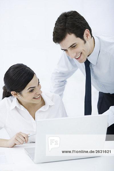 Professioneller Mann mit Blick über die Schulter der Kollegin am Laptop  beide lächelnd