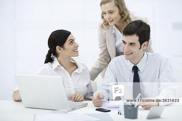 Kollegen versammelt um Laptop-Computer  lächelnd