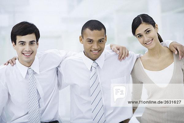 Drei junge Profis mit den Armen um die Schultern  lächelnd vor der Kamera.