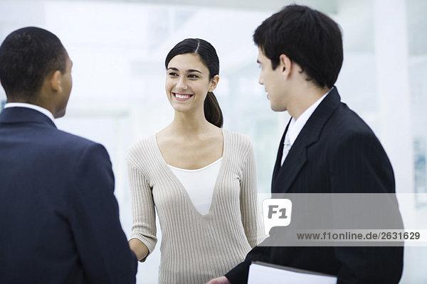 Professionelle Frau steht mit zwei Geschäftsleuten  schüttelt einem Mann die Hand  lächelt