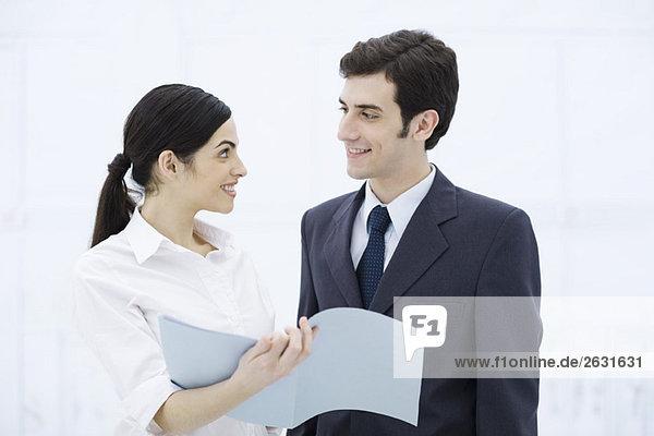 Professionelle Frau zeigt männliches Kollegen-Dokument  beide lächelnd