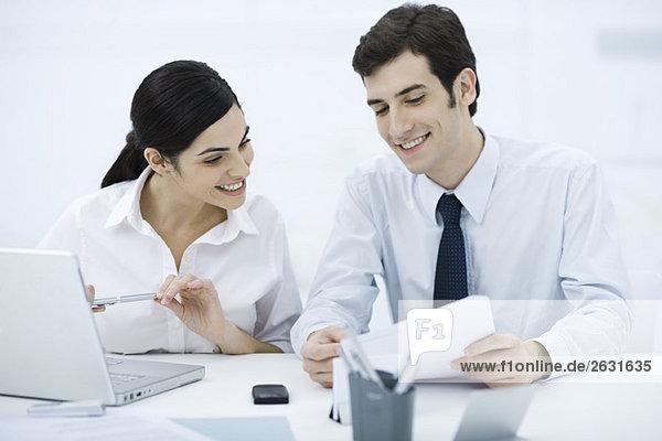 Kollegen sitzen zusammen am Schreibtisch  schauen auf das Dokument  lächeln