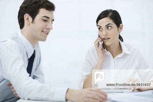 Kollegen sitzen zusammen am Schreibtisch  Frau mit Handy