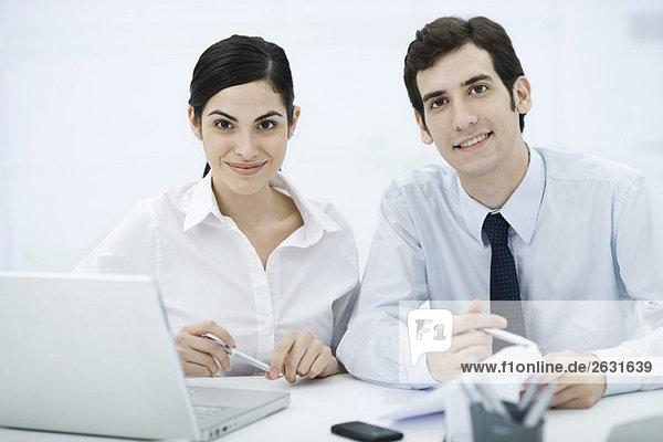 Kollegen sitzen zusammen am Schreibtisch und lächeln in die Kamera.