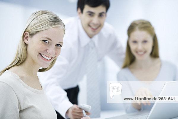 Junge Berufstätige lächelnd vor der Kamera  Kollegen im Hintergrund