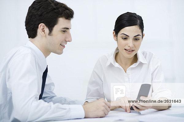 Profis  die das Handy gemeinsam betrachten  lächelnd