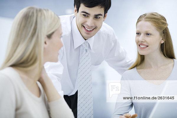 Geschäftsmann lehnt sich rüber  plaudert mit weiblichen Kollegen
