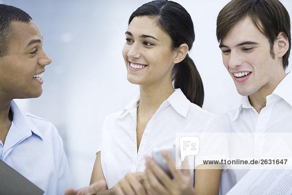 Junge Frau zeigt männlichen Kollegen ihr Handy  lächelnd