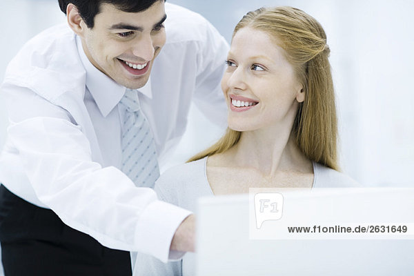 Professioneller Mann lehnt sich über die Schulter der Kollegin  zeigt auf den Laptop  Frau lächelt ihn an.