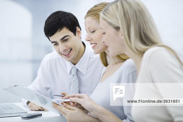 Drei Kollegen lesen Dokument in der Zwischenablage  lächelnd