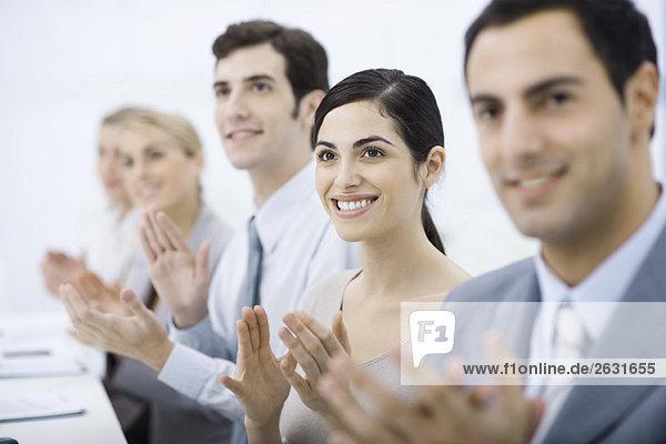 Gruppe von Fachleuten klatschend  lächelnd  auf eine Frau fokussierend