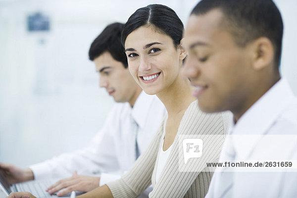 Junge berufstätige Frau sitzt zwischen zwei männlichen Kollegen und lächelt vor der Kamera.