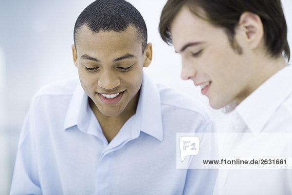 Zwei junge Männer  die lächelnd nach unten schauen.