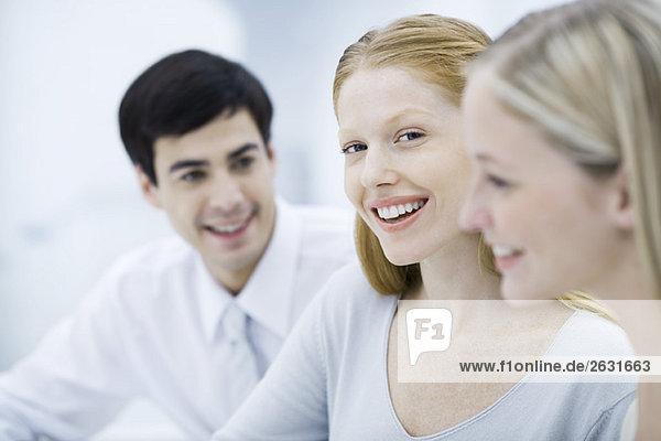 Junge Berufsfrau zwischen zwei Kollegen  lächelnd vor der Kamera