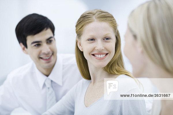Junge berufstätige Frau lächelt Kollegin an  Nahaufnahme
