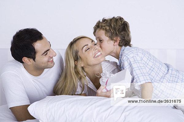Frau im Bett liegend mit Mann und Sohn  Geschenk haltend  Junge küssend ihre Wange