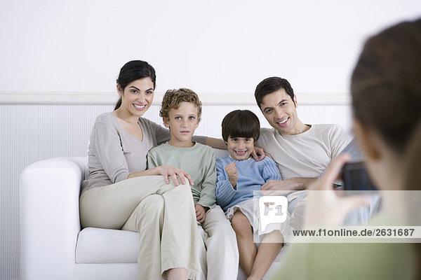 Familie sitzt auf dem Sofa  posiert für ein Foto von der Tochter