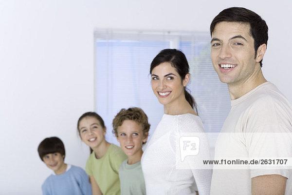 Familie aufgereiht am kürzesten bis am höchsten  Vater anschauend  Vater lächelnd vor der Kamera
