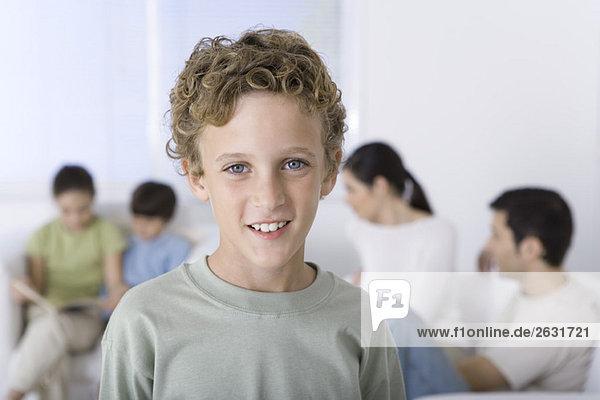Porträt eines lächelnden Jungen  Familie im Hintergrund sitzend