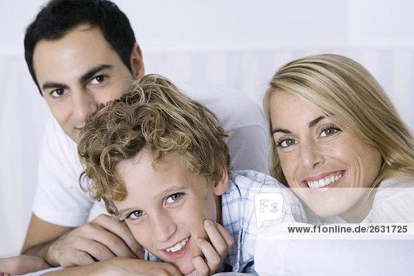 Kleiner Junge entspannt sich mit seiner Mutter und seinem Vater  alle lächelnd vor der Kamera.