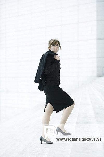 Geschäftsfrau  Jacke auf der Schulter  die Stufen hinaufgeht