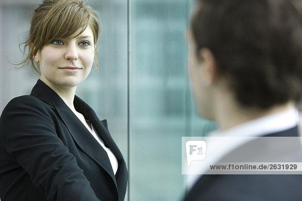 Geschäftsfrau und Geschäftsmann treffen sich und geben sich die Hand.