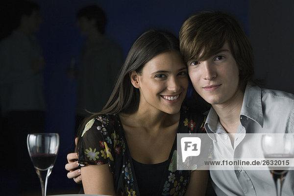 Paar sitzende Wange an Wange  lächelnd vor der Kamera  Portrait